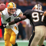 Brett Favre attempts to avoid a potential sack by the Saints Renaldo Turnbull.