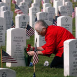 Diane Holt places roses at the grave of her stepfather, Charles Maples Jr.,  Monday morning at the Biloxi National Cemetery. Maples was in the U. S. Navy  and served in Korea and Vietnam.