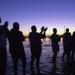 TIM ISBELL/SUN HERALDJames Stowe (foreground) leads fellow marchers into the water to sing We   Shall Overcome and a prayer Tuesday evening near the Biloxi Lighthouse. The   symbolic gesture was in honor of Dr. Gilbert Mason's wade in during 1963.